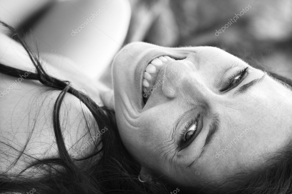 Attractive mid adult Caucasian woman lying on back smiling and looking at viewer.  Stock Photo #9330619
