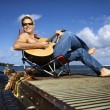 Royalty-Free Stock Photo: Young Man Sitting Lakeside and Playing Guitar