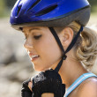 Woman putting on helmet. — Stock Photo