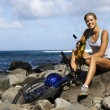 Attractive Young Woman Sitting With Bicycle on Rocky Beach — Stock Photo
