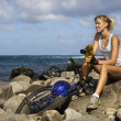 Stock Photo: Attractive Young WomSitting With Bicycle on Rocky Beach