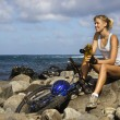 Attractive Young WomSitting With Bicycle on Rocky Beach — Stock Photo #9363467