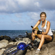 Attractive Young Woman Sitting With Bicycle on Rocky Coast — Stock Photo