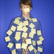 Caucasian teen boy covered with sticky notes. - 图库照片