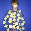 Caucasian teen boy covered with sticky notes. - Stockfoto