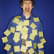 Caucasian teen boy covered with sticky notes screaming. — Stock Photo