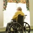 Elderly Man in Wheelchair by Window - Foto Stock