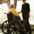 Elderly Man in Wheelchair and Young Woman — Photo