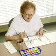 Mature woman painting. - Stock Photo