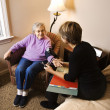 Elderly Woman Having Blood Pressure Taken - Stock Photo