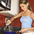 Attractive Young Woman in Kitchen Cooking - Stock Photo