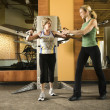 Woman helping woman excercise. — Stock Photo