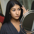 Young woman looking in mirror. — Stock Photo