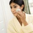 Young woman applying face scrub. — Stock Photo #9367123