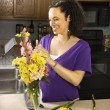 Pregnant woman arranging flowers. — Stock Photo