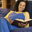 Pregnant smiling woman reading. - Stock Photo