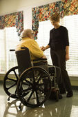 Elderly Man in Wheelchair and Young Woman — Stock Photo