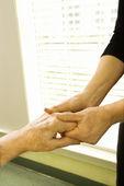 Woman holding mature woman's hand. — Stock Photo