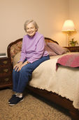 Mature woman on bed. — Stock Photo