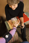 Nurse taking blood pressure. — Stock Photo