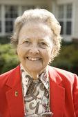 Anciana en capa roja sonriendo al aire libre — Foto de Stock