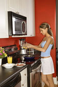 有魅力的年轻女人在厨房里煮早餐 — 图库照片