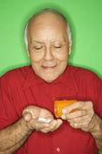 Man emptying pill bottle. — Stock Photo
