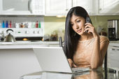 Young Woman Using Laptop and Talking on Cellphone — Stock Photo