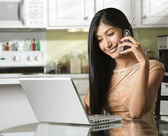 Young Woman Using Laptop and Talking on Cellphone — Foto de Stock