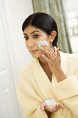 Young woman applying face scrub. — Stock Photo