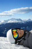 Boy snowboarder lying on mountain. — Stock Photo