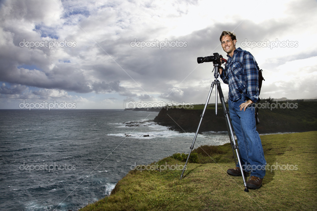 Caucasian mid-adult male standing with camera on tripod looking at viewer on cliff overlooking the ocean in Maui, Hawaii.  Stock Photo #9363421