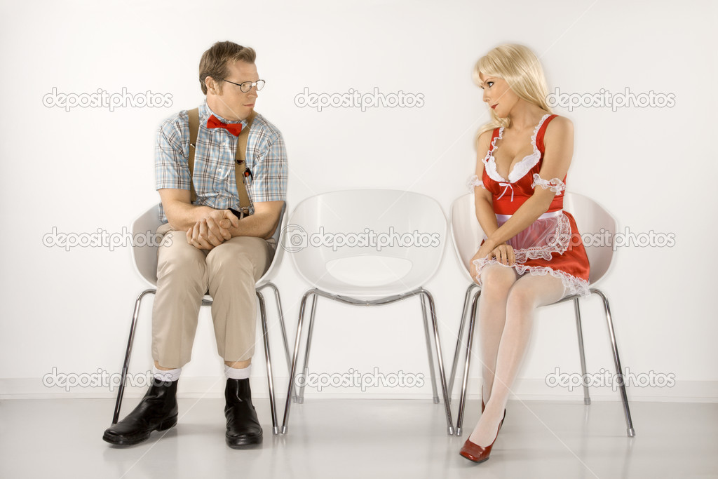 Caucasian young man dressed like nerd and Caucasian young blonde woman in french maid outfit sitting and looking at eachother.  Stock Photo #9364248