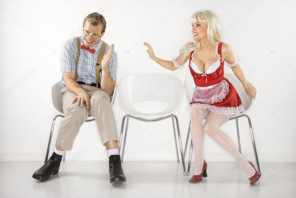 Caucasian young blonde woman sitting reaching over to shy Caucasian young man dressed like nerd. — Stock Photo #9364250