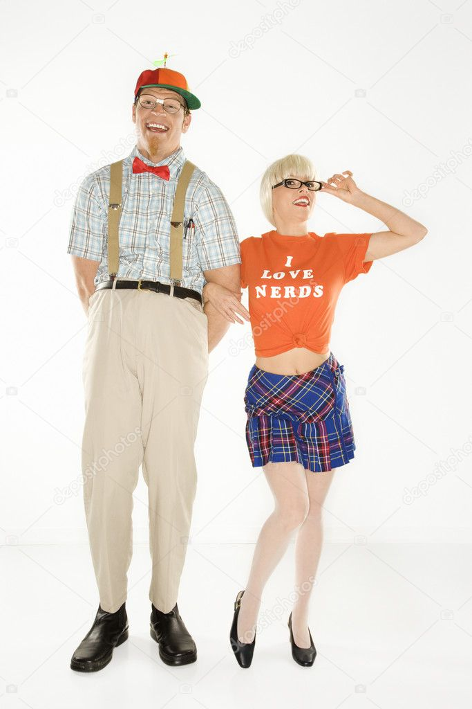 Caucasian young man dressed like nerd wearing propeller hat with blonde Caucasian young woman in nerdy eyeglasses and tshirt reading I love nerds and plaid skirt. — Stock Photo #9364268