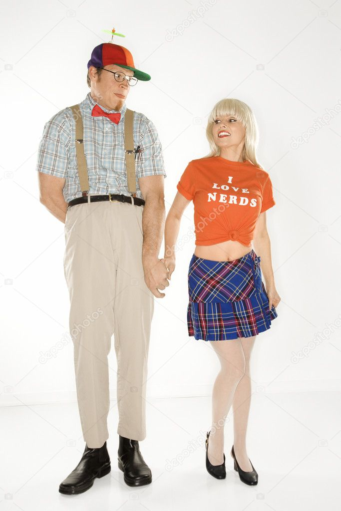 Caucasian young man dressed like nerd wearing propeller hat holding hands with Caucasian blonde young woman wearing tshirt reading I love nerds and plaid skirt. — Stock Photo #9364269
