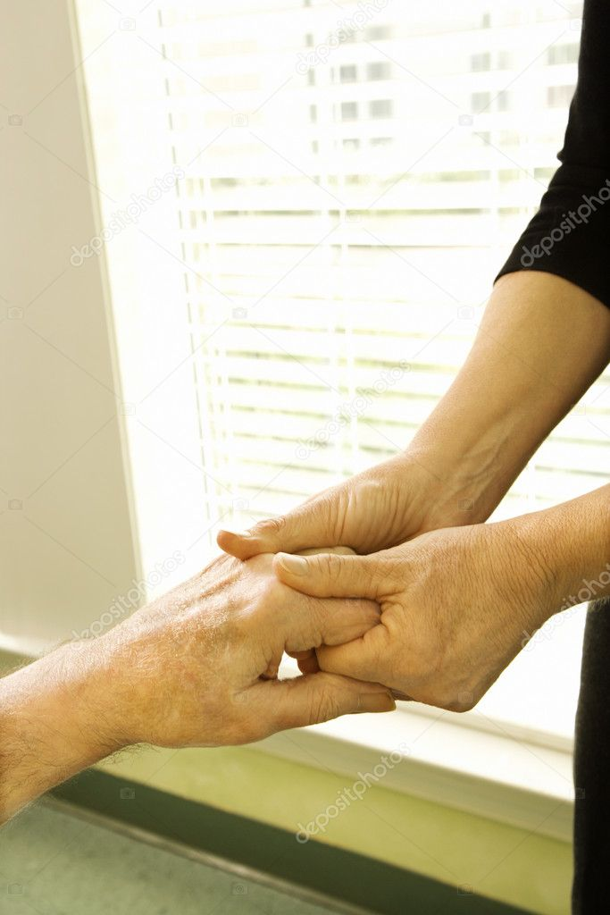 Caucasian female nurse massaging arthritic hands of elderly man at retirement community center. — Stock Photo #9364312