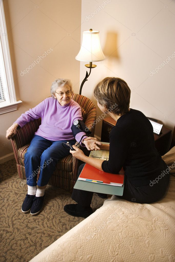 Nurse checking an elderly woman's blood pressure in assisted living home. Vertical shot. — Stock Photo #9364341