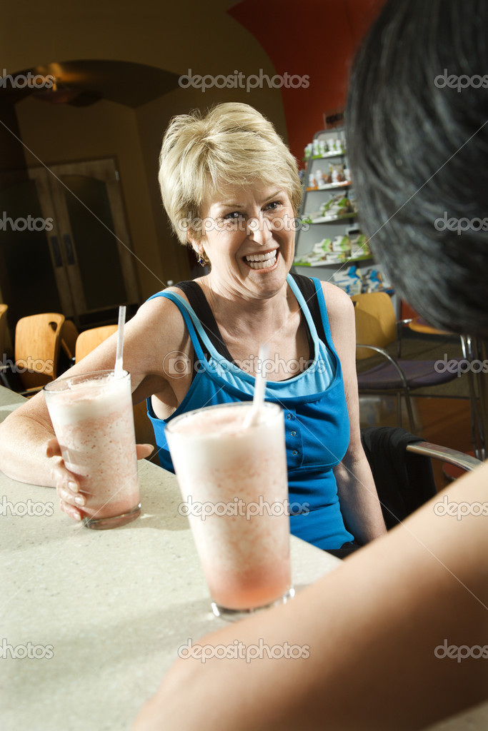 Mature Caucasian adult females sitting at table in health club cafeteria. — Stock Photo #9365951