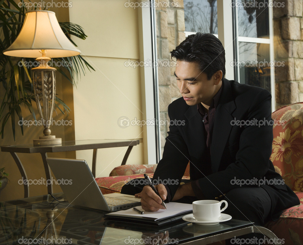 A young Asian businessman looking at a laptop computer whiles taking notes on a notebook. Horizontal shot. — Stock Photo #9366156