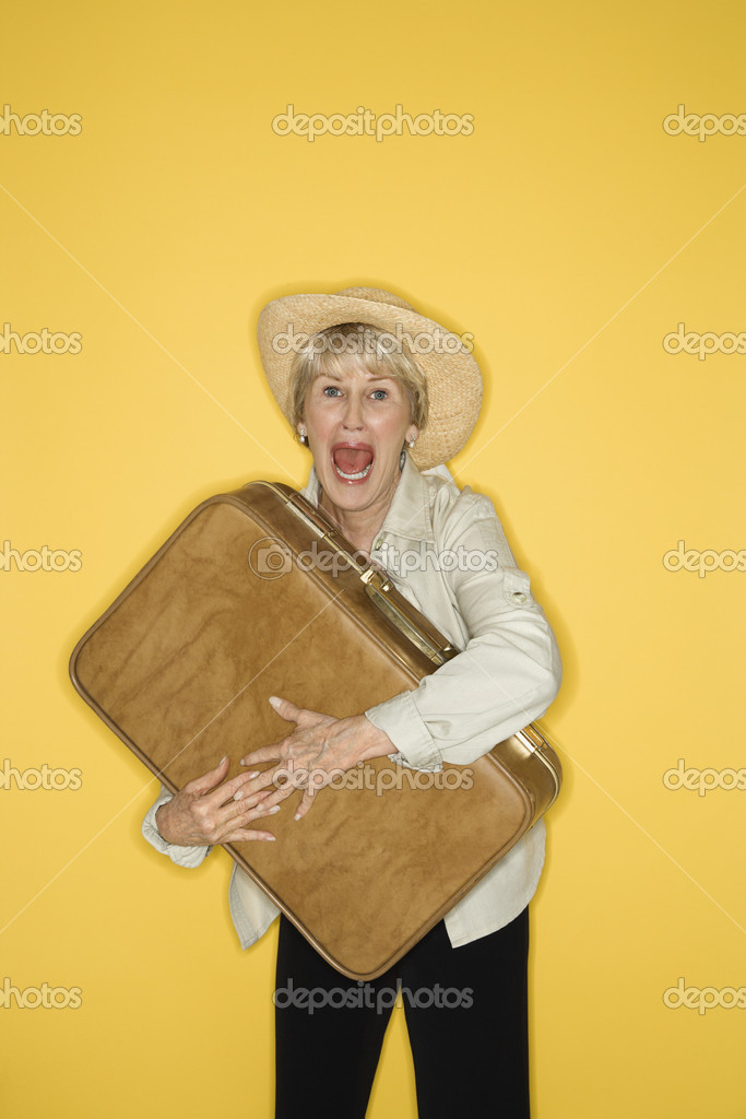 Caucasian mature adult female grasping suitcase. — Stock Photo #9366440