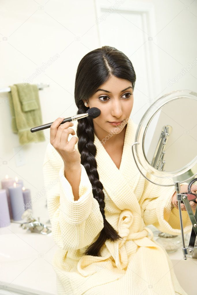A young woman wearing a bathrobe is sitting on the bathtub  in front of a mirror and applying makeup. Her long dark hair is braided and hanging over her shoulder. Vertical shot. — Stock Photo #9367077
