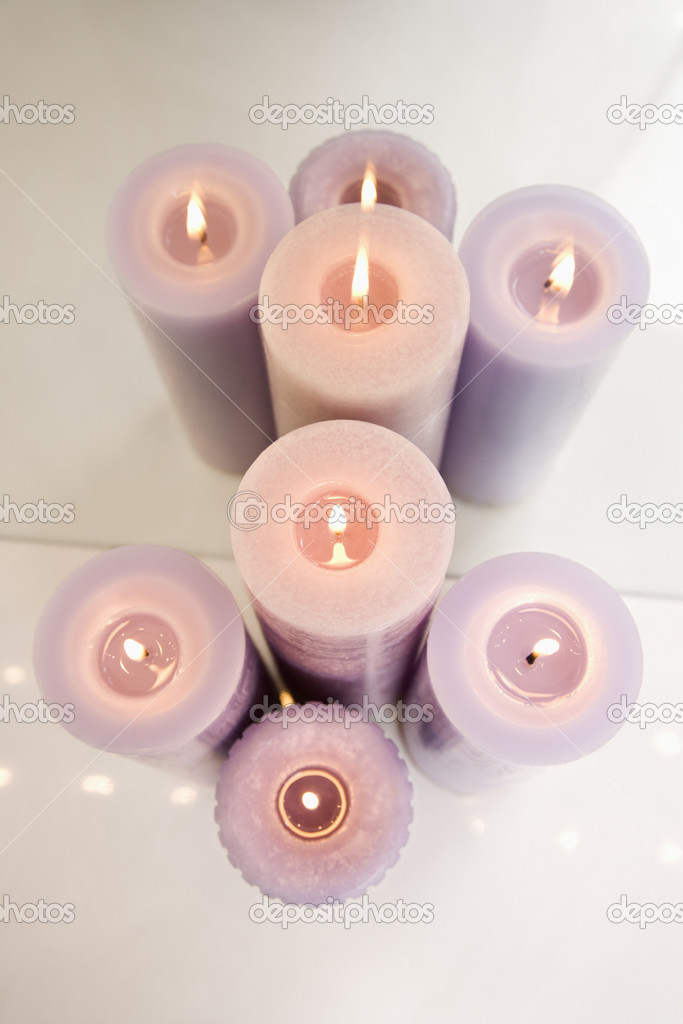 Overview of purple burning candles in front of mirror. — Stock Photo #9367118