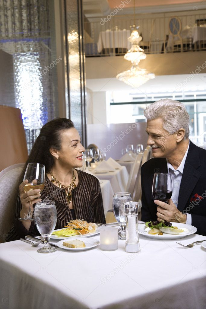 Caucasian mature adult male and prime adult female sitting at restaurant table. — Stock Photo #9367567