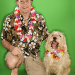 Stock Photo: Man and dog wearing leis.