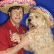 Stock Photo: Dog and man wearing sombreros.