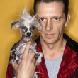 Stock Photo: Man holding Chinese Crested dog.
