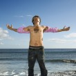 Young Man Standing on Ocean Rock with Arms Outstretched — Stock Photo