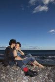 Couple snuggling on beach. — Stock Photo