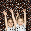 Girl twins  with arms raised. - Photo